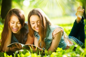 Happy teenage girls reading a magazine outdoors